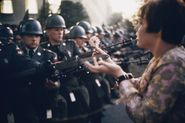 17-year-old Jan Rose Kasmir offers a flower to soldiers during the Pentagon anti-war protest in 1967.