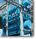 How are plate exchangers used in an ammonia refrigeration system?